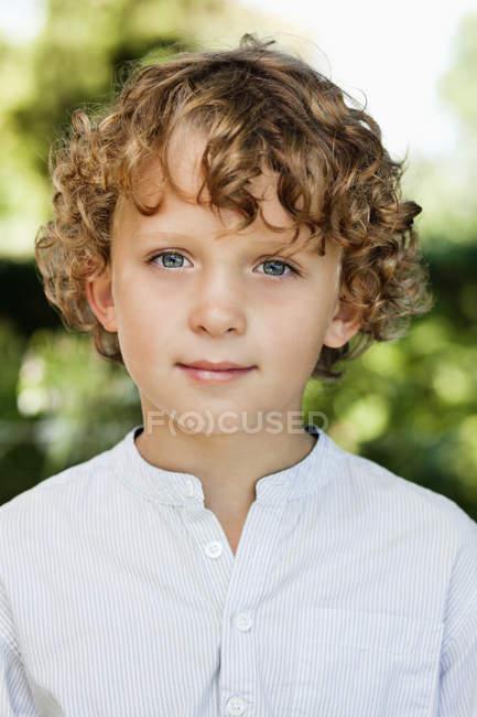 Крупный план улыбающегося мальчика с вьющимися волосами в белой рубашке — стоковое фото