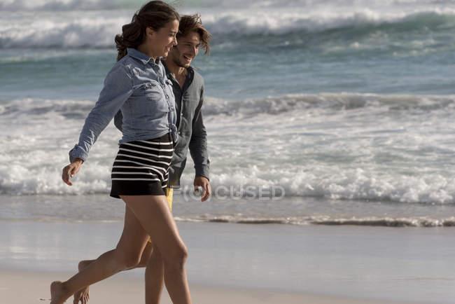 Feliz romântico jovem casal andando na praia — Fotografia de Stock