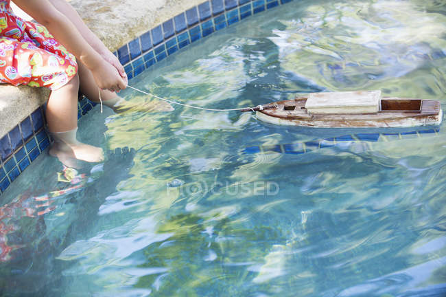 Girl sitting at edge of swimming pool with toy boat in water — Stock Photo