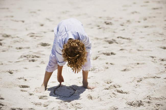 Garçon jouer avec le sable sur la plage ensoleillée — Photo de stock