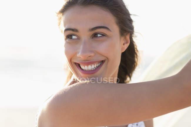 Портрет посміхаючись молоду жінку на вулиці у sunlight — стокове фото