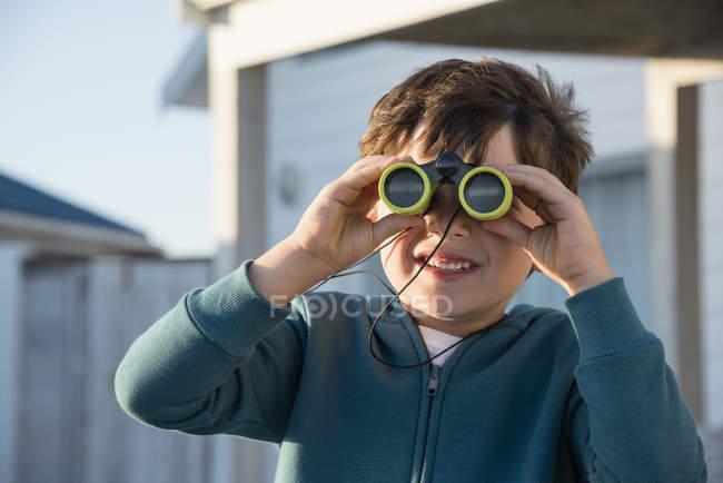 Happy little boy looking through binoculars outdoors — Stock Photo