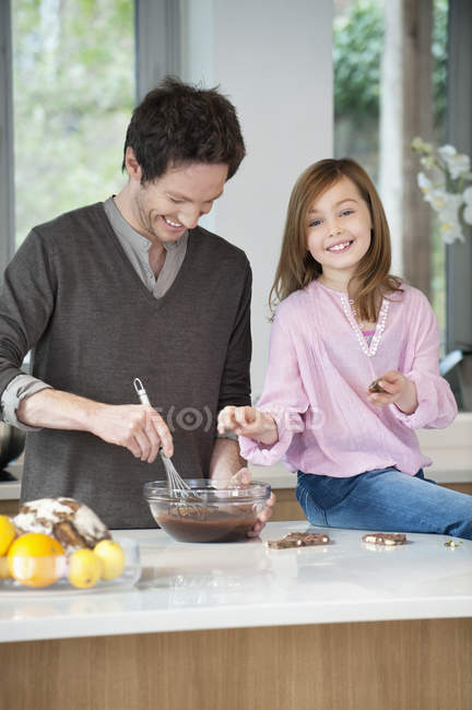 Man stirring a mixture in bowl with daughter — стоковое фото