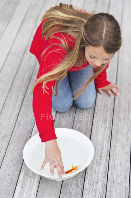 Girl touching red fish in bowl on wooden pier — Stock Photo