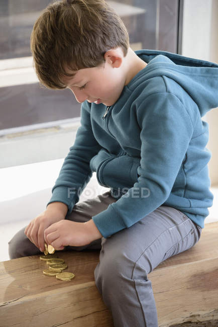 Little boy playing with coins — Stock Photo