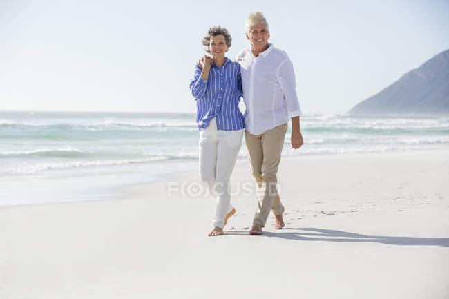 Обнимая счастливую пару, идущую по песчаному пляжу — стоковое фото