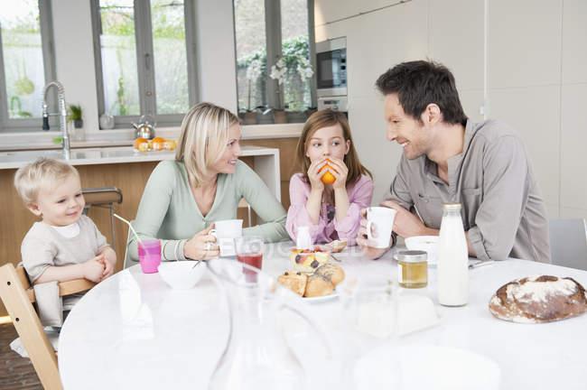 Happy family having fun at breakfast table — Stock Photo