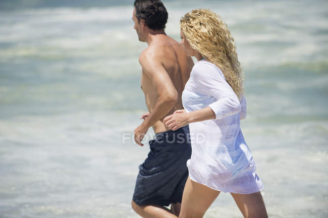 Mid adult couple running on beach together — Stock Photo
