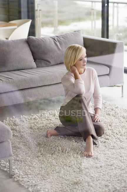 Giovane donna che si siede sul tappeto in salotto moderno e pensiero — Foto stock