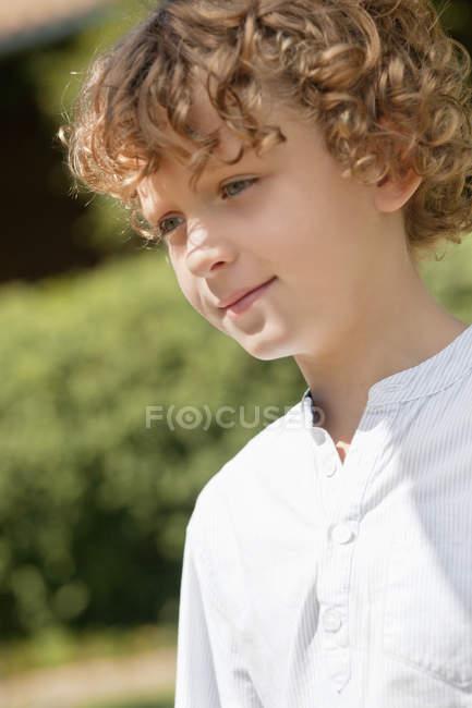 Nahaufnahme eines lächelnden jungen mit lockiges Haar Tagträumen in der Natur — Stockfoto