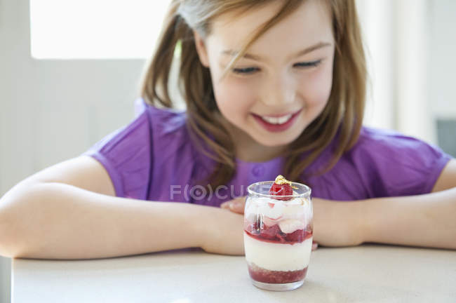 Smiling little girl looking at a glass of ice cream — Stock Photo