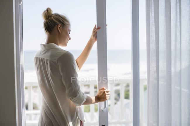 Расслабленная молодая женщина, стоящая у окна дома — стоковое фото