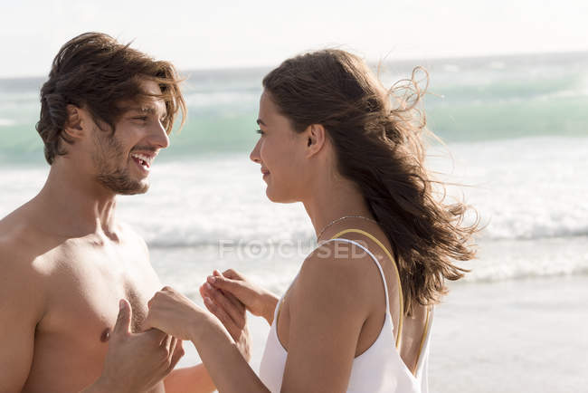 Young couple romancing on beach with wavy sea on background — Stock Photo