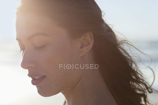 Close-up of thoughtful young woman with eyes closed on beach — Stock Photo