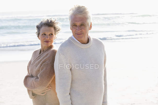 Relaxed thoughtful senior couple standing on beach together — Stock Photo