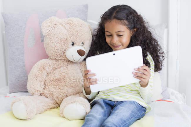 Feliz niña con tableta digital de oso de peluche en la cama - foto de stock