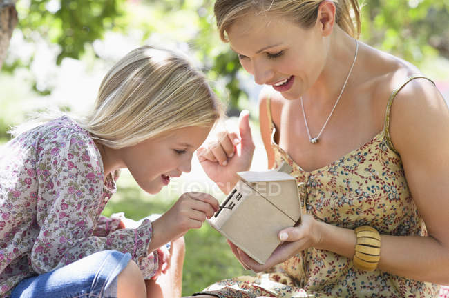 Little girl and mother holding dollhouse outdoors — Stock Photo