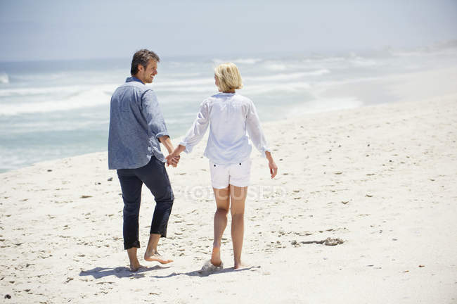 Vue arrière d'un couple romantique marchant sur la plage se tenant la main — Photo de stock