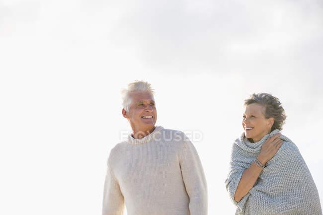 Primer plano de la pareja sonriente caminando juntos al aire libre - foto de stock