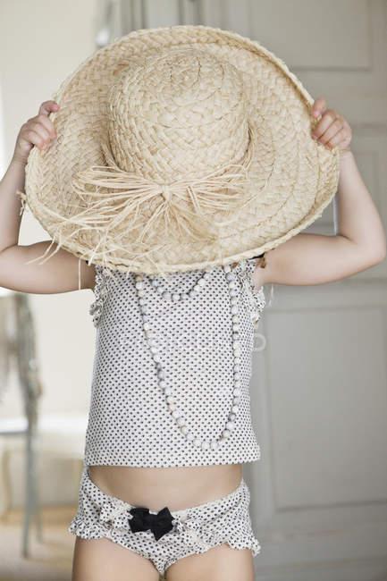 Cute little girl wearing oversized straw hat — Stock Photo