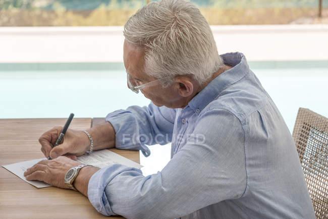 Senior erledigt Papierkram am Pool — Stockfoto