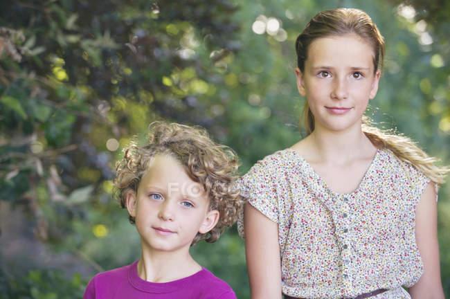 Retrato de irmãos bonitos de pé juntos no jardim de verão — Fotografia de Stock