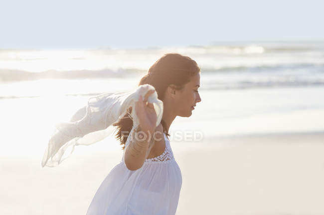Relaxed young woman walking on beach with pareo — Stock Photo