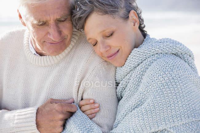 Close-up do casal sênior pensativo, abraçando na praia — Fotografia de Stock