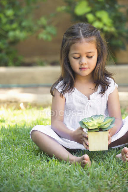 Cute little girl holding potted plant while sitting on grass — Stock Photo