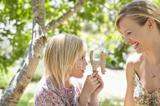 Menina e mãe olhando para o brinquedo ao ar livre — Fotografia de Stock