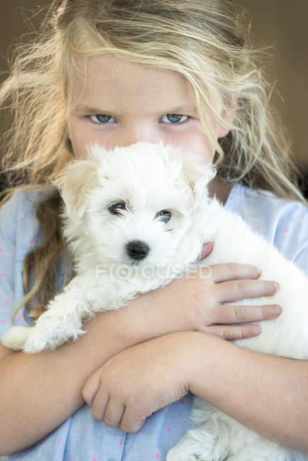 Портрет милой маленькой девочки, обнимающей щенка — стоковое фото