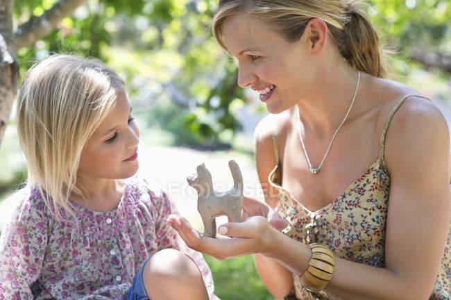 Menina e mãe olhando para o brinquedo na mão ao ar livre — Fotografia de Stock
