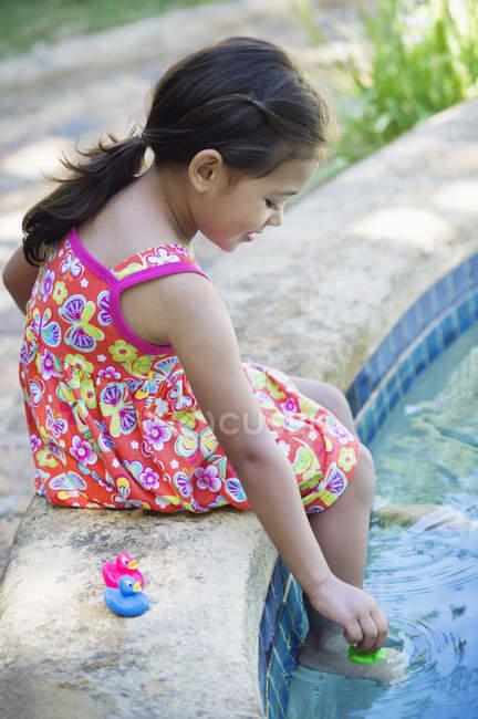 Bambina che gioca con le anatre di gomma sul bordo della piscina — Foto stock