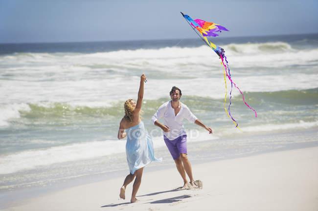 Couple having fun with flying kite on beach — Stockfoto