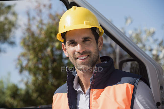 Portrait of smiling male engineer standing at van — Stock Photo