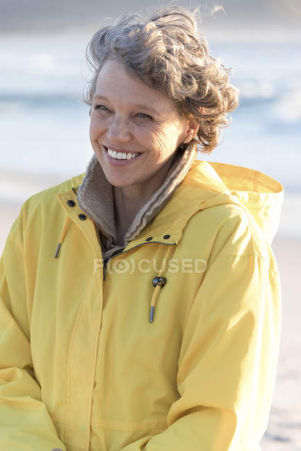 Portrait of happy mature woman in raincoat standing on beach — Stock Photo