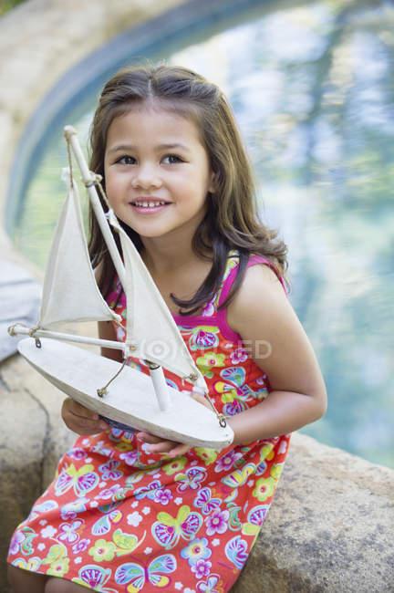 Улыбающаяся маленькая девочка сидит у бассейна с игрушечной лодкой — стоковое фото
