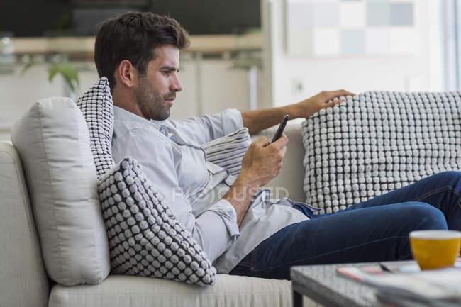 Nachdenklicher Mann sitzt auf Couch und nutzt Smartphone — Stockfoto