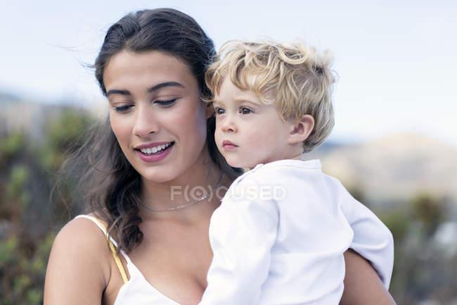 Счастливая женщина носит ребенка на открытом воздухе — стоковое фото