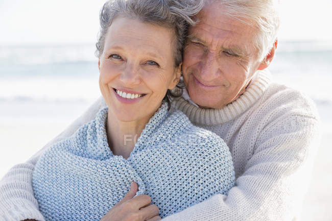 Happy man embracing wife from behind on beach — Stock Photo