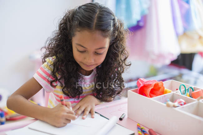 Concentrated little girl doing homework on table — Stock Photo