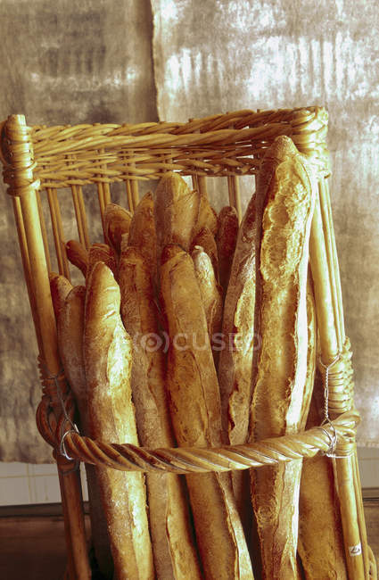 Freshly baked French baguettes in basket — Stock Photo