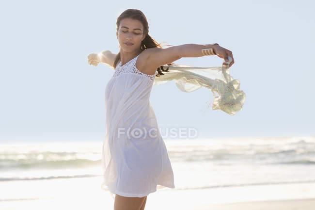 Розслабленої молода жінка з руки розкритими насолоджуючись на пляжі — стокове фото