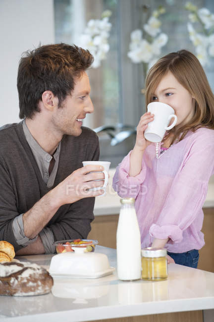 Man drinking tea with happy daughter in kitchen — Stock Photo