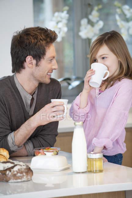 Mann trinkt Tee mit glücklicher Tochter in der Küche — Stockfoto