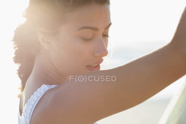 Primer plano de la joven reflexiva con los ojos cerrados posando a la luz del sol - foto de stock