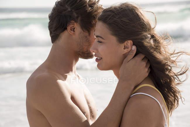 Молодая пара романсы на пляже с волнистым морем на заднем плане — стоковое фото