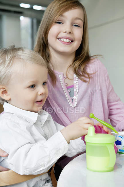 Portrait of smiling girl with brother posing at home — Stock Photo