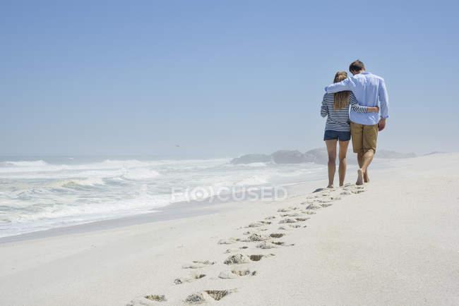 Вид сзади романтичной пары, ходить на пляже под голубым небом с след в песке — стоковое фото