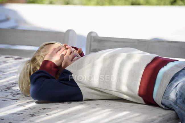 Menino brincalhão deitado na mesa ao ar livre com as mãos cobrindo os olhos — Fotografia de Stock